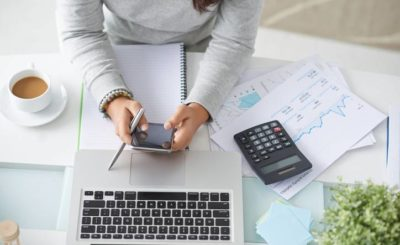Financial manager using smartphone at her workplace, view from the top